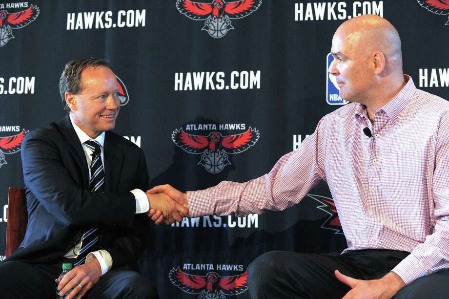 Hawks general manager Danny Ferry (right), a former Spurs player and vice president of basketball operations, shakes hands with new coach Mike Budenholzer, a Spurs assistant. Photo: Dave Tulis / Associated Press
