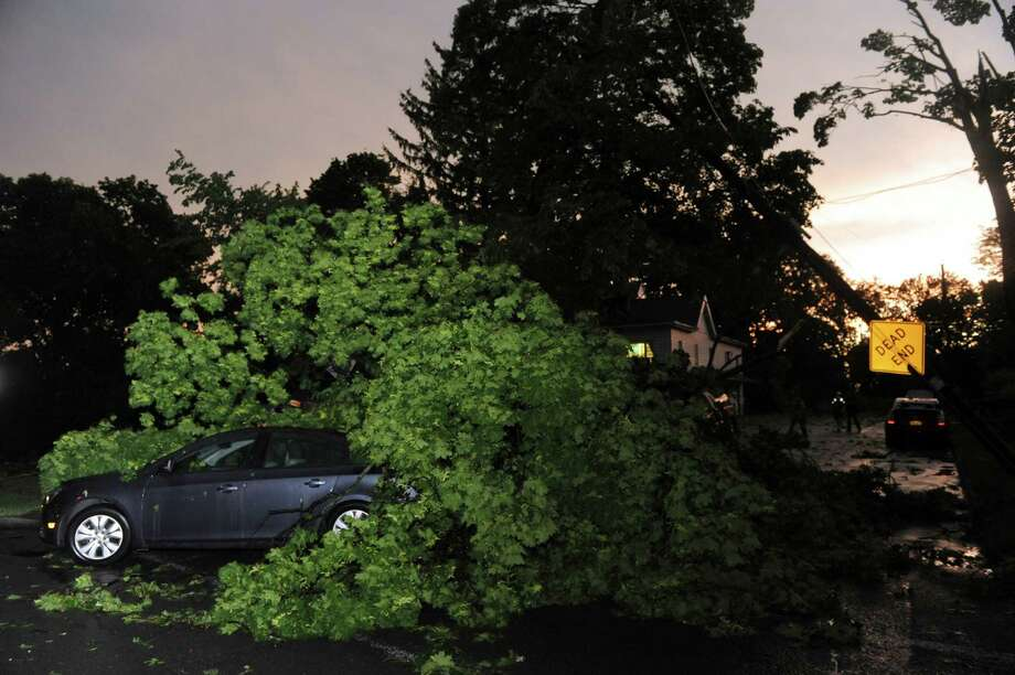 A downed tree sits on a car blocking the entrance to Farview Avenue and Oakwood Avenue on Wednesday May 29, 2013 in Troy, N.Y. (Michael P. Farrell/Times Union) Photo: Michael P. Farrell