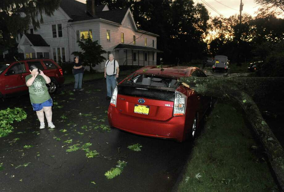 A downed tree limb sits atop a car on Farview Avenue Wednesday May 29, 2013 in Troy, N.Y. (Michael P. Farrell/Times Union) Photo: Michael P. Farrell
