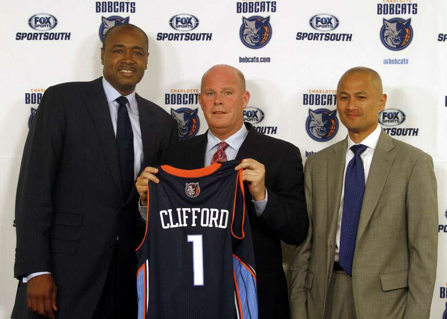 New Bobcats coach Steve Clifford holds a jersey bearing his name while standing with president of basketball operations Rod Higgins on Wednesday. Photo: Nell Redmond / Associated Press