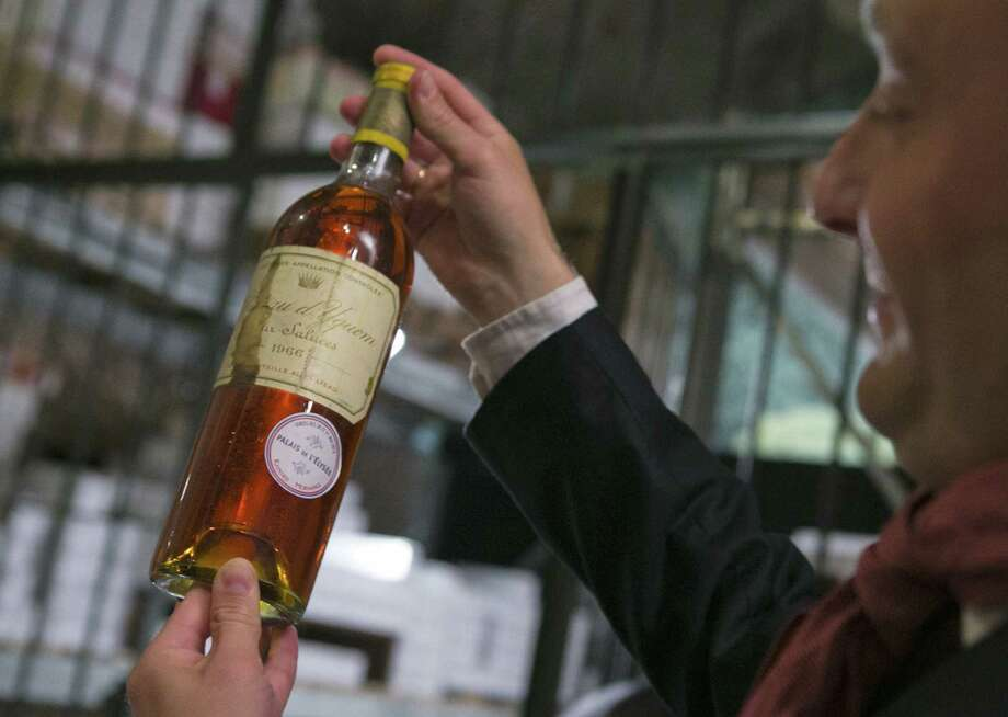 A bottle of 1966 Chateau d'Yquem premier cru Sauternes is one of the ritzy bottles of wine being put on auction by the French presidential palace. Photo: Jacques Brinon / Associated Press