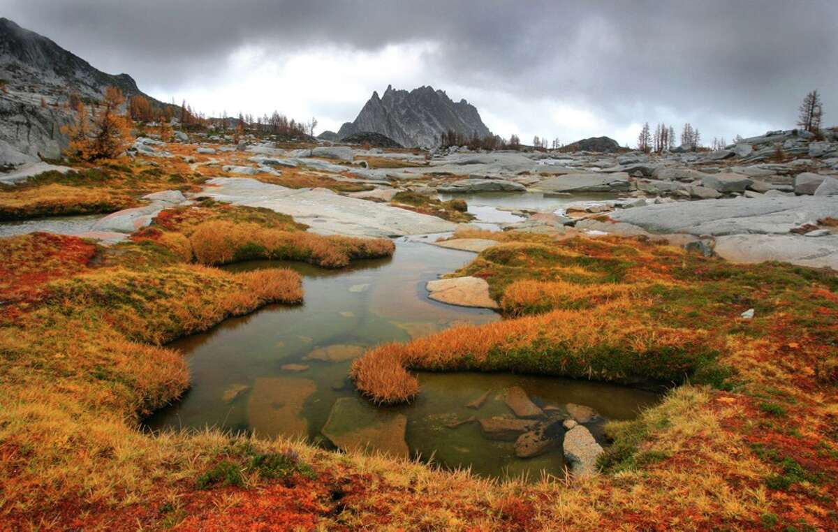 Storm clouds allow a glimpse of Prusik Peak during a hike in The Enchantment Lakes Basin of the Alpine Lakes Wilderness Area.  The Okanogan-Wenatchee National Forest conducts a lottery to pick overnight visitors between May 15 and October 31.  Intrepid athletes run through all 17 miles in a day. (Joshua Trujillo, Seattle Post-Intelligencer file)