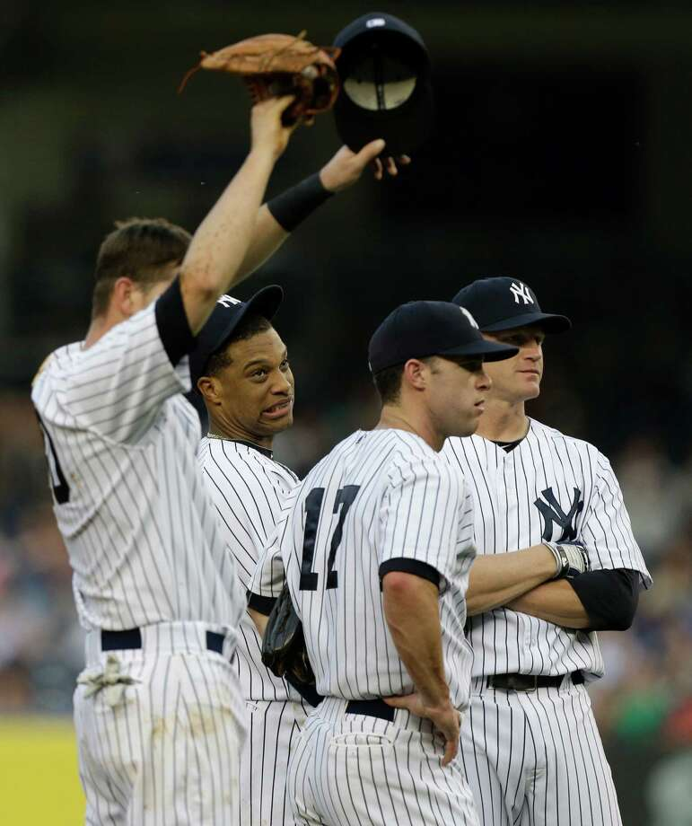New York Yankees second baseman Robinson Cano, second from left, and teammates react after starting pitcher David Phelps allowed five runs in the first inning of an interleague baseball game against the New York Mets at Yankee Stadium in New York, Wednesday, May 29, 2013.  Yankees shortstop Reid Brignac, left, third baseman Jayson Nix (17) and first baseman Lyle Overbay look on. Photo: Kathy Willens