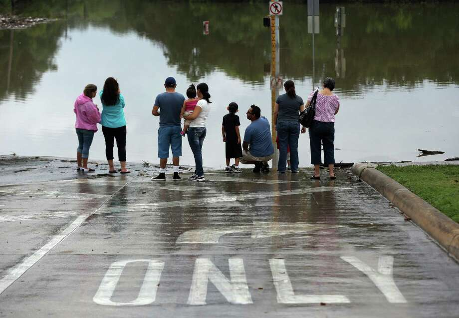 Onlookers gather along a flooded intersection ast Sunday. The storms 