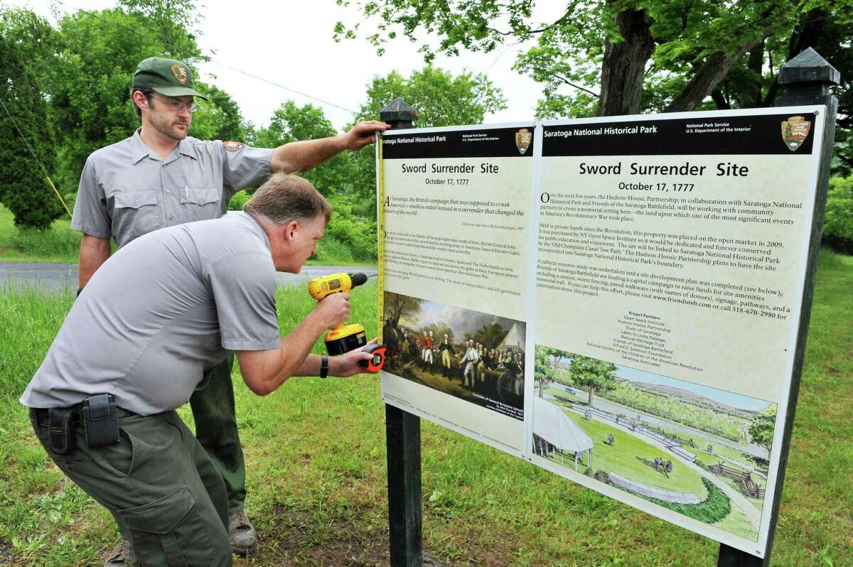 Saratoga National Historical Park maintenance staff members Charles Koffman, left, and Jeff Wells erect an historic marker at the park's newly acquired satellite property along Rt. 4, in the Town of Saratoga Wednesday May 29, 2013. The site is where British Gen. Burgoyne surrendered his sword to Gen. Gates at America's first major victory in the Revolutionary War. (John Carl D'Annibale / Times Union)