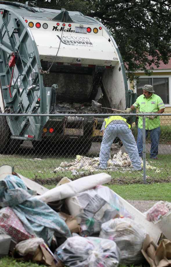 Household debris is cleaned up Wednesday May 29, 2013 on the 10,000 block of Espada Road. Residents in the area are clearing out thier homes of items damaged by last weekend's flooding that dumped more than ten inches of rain in the San Antonio area. Photo: JOHN DAVENPORT, SAN ANTONIO EXPRESS-NEWS / ©San Antonio Express-News