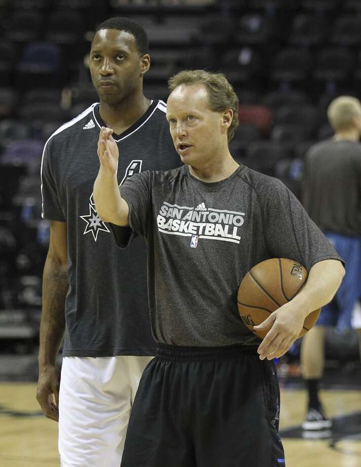 Spurs' assistant coach Mike Budenholzer (right) offers instruction to forward Tracy McGrady during shoot-around prior to the start of the game against the Minnesota Timberwolves on Wednesday, Apr. 17, 2013. McGrady was recently signed by the Spurs. (Kin Man Hui / San Antonio Express-News)