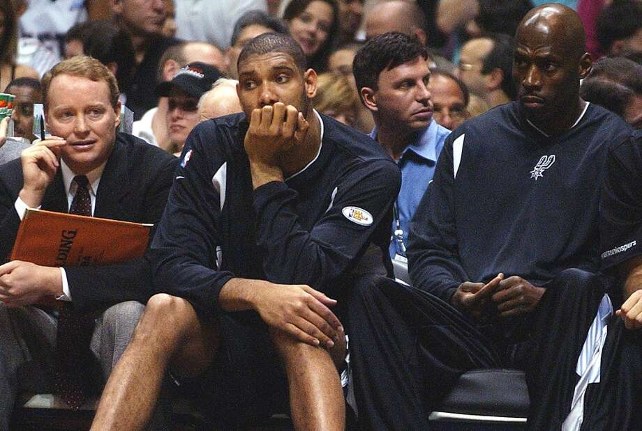 Spurs Tim Duncan sits with three fouls during second quarter of game four of the NBA Finals at the Continental Airlines Arena in New Jersey on Wednesday, June 11, 2003. Assistant coach Mike Budenholzer, left and player Kevin Willis look on. (Kin Man Hui / San Antonio Express-News)