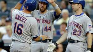 New York Mets' John Buck (44) greets center fielder Rick Ankiel (16) after they scored on Ike Davis's first inning, two-run single in an interleague baseball game against the New York Yankees at Yankee Stadium in New York, Wednesday, May 29, 2013. On-deck batter Mike Baxter (23) looks on. (AP Photo/Kathy Willens)