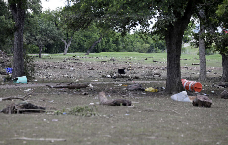Junk left by the floodwaters covers the fourth and fifth fairways as workers continue to clean debris from the Olmos Golf Course. About 80 percent of the layout, which weathered 10 inches of rain, was submerged by the deluge over the weekend. Photo: Photos By Tom Reel / San Antonio Express-News