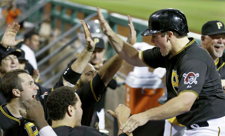 Travis Snider (right) is greeted in the dugout by his Pittsburgh teammates after scoring in the eighth. Photo: Keith Srakocic / Associated Press