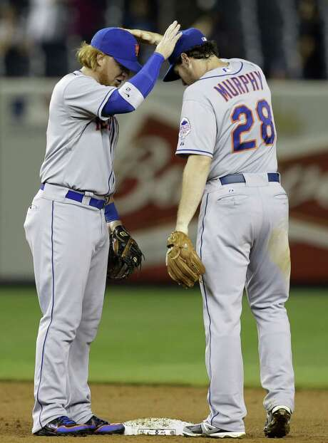 The Mets' Justin Turner and Daniel Murphy trade celebratory head taps after beating the Yankees. Photo: Kathy Willens / Associated Press