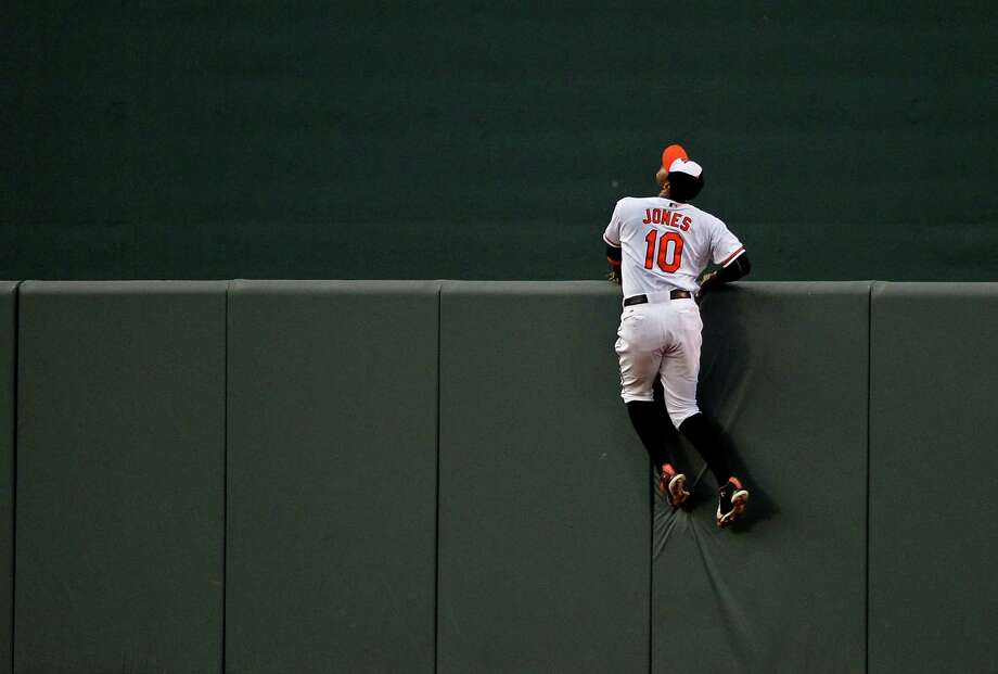 The Nationals' Ryan Zimmerman and the Orioles' Adam Jones, right, watch the second of Zimmerman's three home runs from vantage points some 400 feet apart. Photo: Patrick Smith, Stringer / 2013 Getty Images