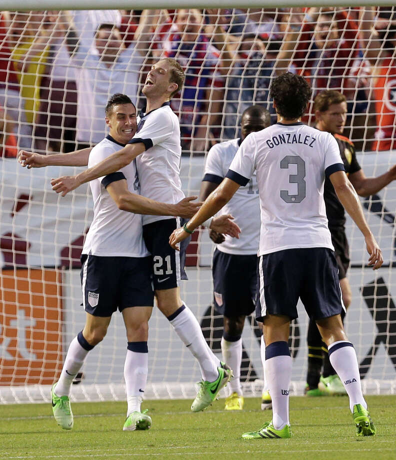 Former Dynamo defender Geoff Cameron, left, celebrates with Clarence Goodson after Cameron scored his first U.S. national team goal that was one of the few bright spots in a 4-2 loss to Belgium. Photo: Tony Dejak, STF / AP