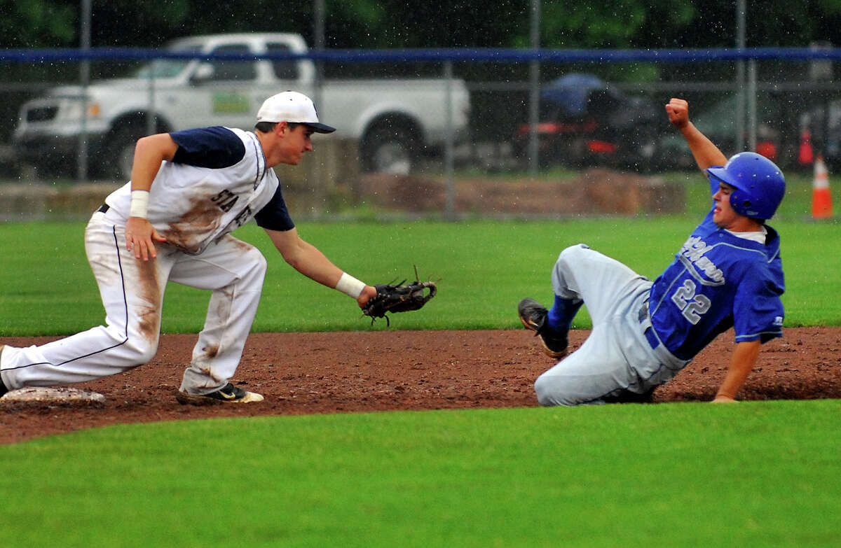 Staples' Sam Ellinwood prepares to tag out West Haven's Tyler Gambardella, during FCIAC Class LL state first round baseball action in West Haven, Conn. on Tuesday May 28, 2013. Only one inning was completed before the game was suspended due to rain.