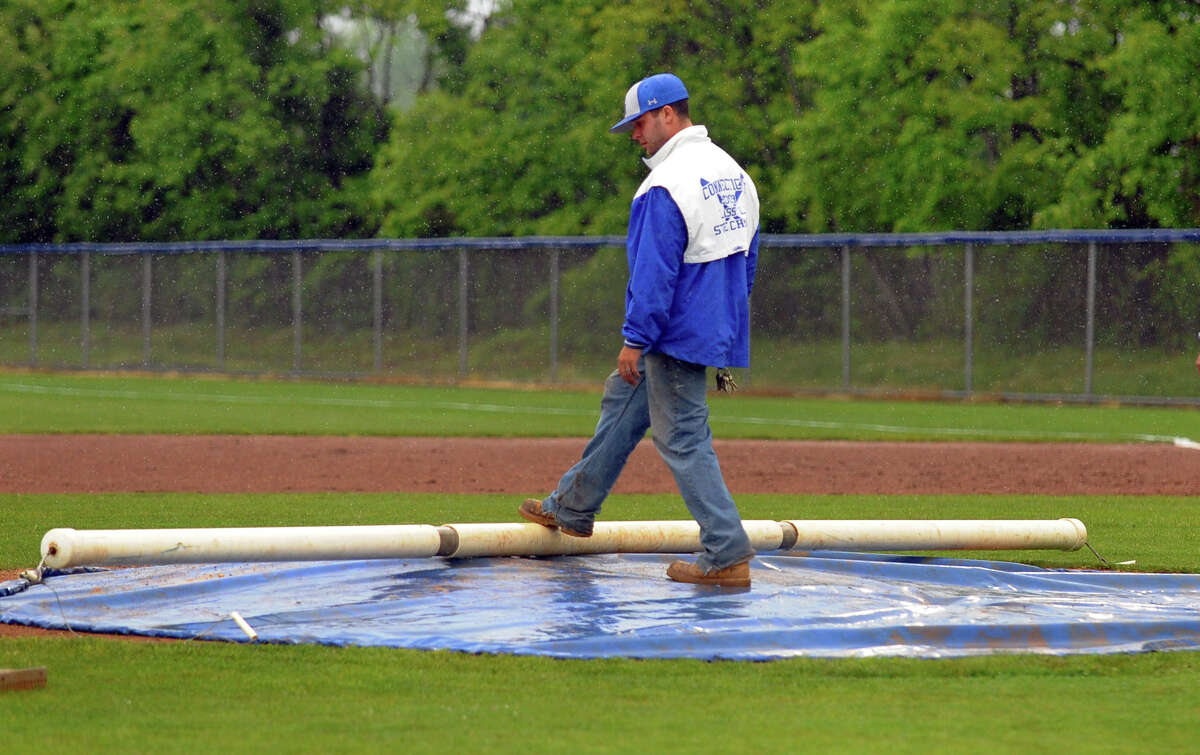A grounsdkeeper lays out a tarp on the pitcher's mound during a rain delay during FCIAC Class LL state first round baseball action between Staples and West Haven in West Haven, Conn. on Tuesday May 28, 2013. A fwew minutes later the game was suspended.