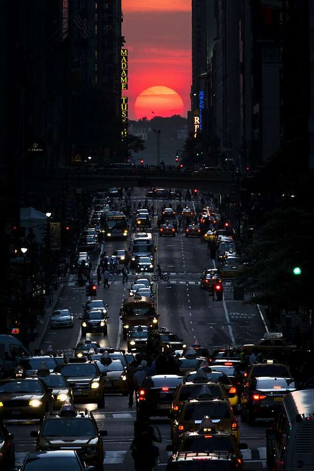 "The sun sets along 42nd Street in Manhattan during an annual phenomenon known as ""Manhattanhenge,"" when the sun aligns perfectly with the city's transit grid, Wednesday, May 29, 2013, in New York. (AP Photo/John Minchillo) Photo: John Minchillo, Associated Press"