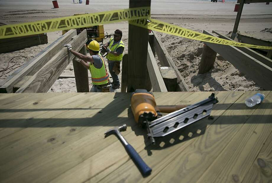 Workers repair a section of the boardwalk in Seaside Heights, New Jersey, U.S., on Wednesday, May 29, 2013. Sandy, which came ashore near Atlantic City, killed dozens of people and destroyed more than 365,000 homes in the state. Christie has said it will cost $36.9 billion for repairs and to prevent devastation from future storms. Photographer: Scott Eells/Bloomberg Photo: Scott Eells, Bloomberg