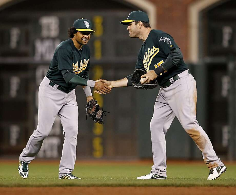 A third straight win over the Giants ends with a congratulatory handshake between A's Coco Crisp (left) and Seth Smith. Photo: Brant Ward, The Chronicle