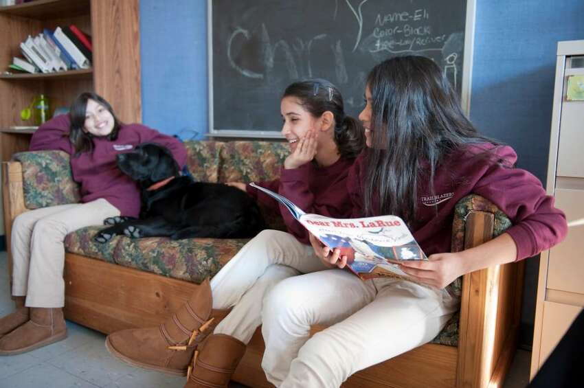 Alileen Barillas, Cintia Enamorado and Joselyn DeLeon right, all 11 and 6 graders at Trailblazers Academy students read out loud in the company of Eli a black lab retriever puppy Tuesday Jan. 12, 2009. For about six weeks now, struggling readers at the charter middle school have practiced in front of the least judgmental of listeners, a dog
