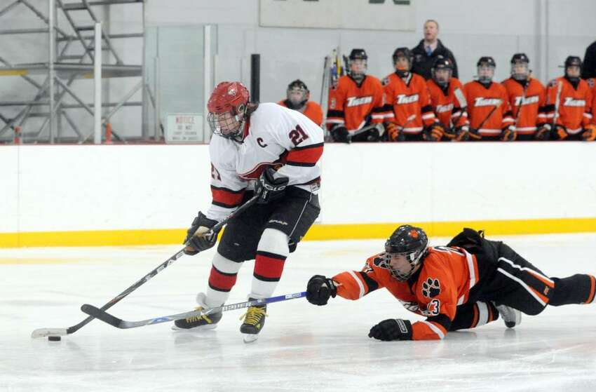 Greenwich captain Ryan Kelly moves beyond Ridgefield's Duncan Morrissey as the Greenwich High School Cardinals host the Ridgefield High School Tigers in a boys hockey game at Dorothy Hamill Tuesday evening, January 12, 2010.