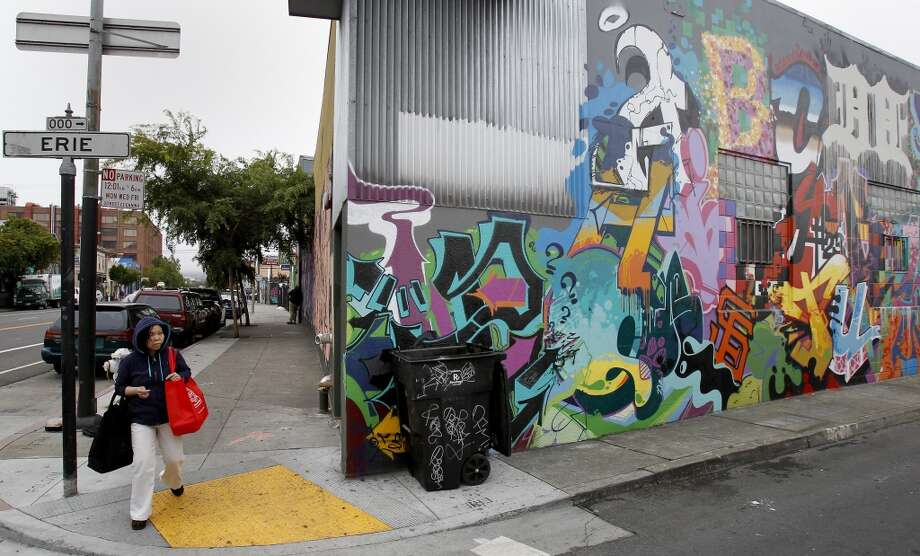 A woman passes the corner of Folsom and Erie streets, where some property owners have agreed to let graffiti artists paint on their buildings for free to deter tagging.