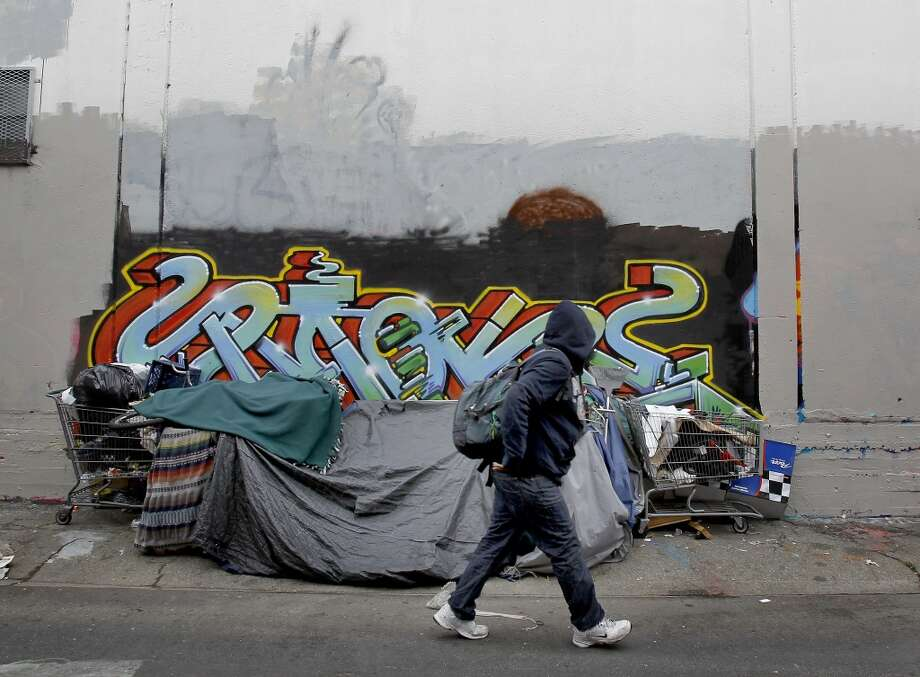 A man walks past a homeless encampment on Erie Street.