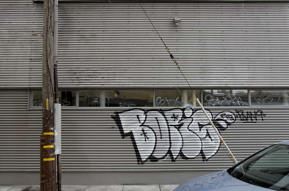 An effort by a business owner at Erie and South Van Ness to paint over a building wall is met by new graffiti.