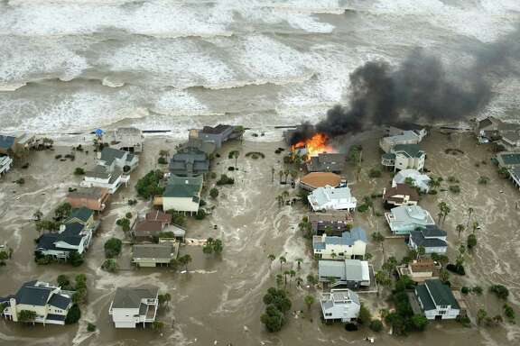 A house is engulfed in flames as water and waves inundate homes on Galveston Island as Hurricane Ike approaches the coast Sept. 12, 2008.