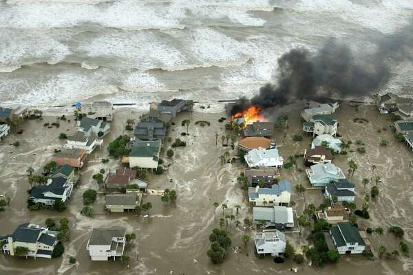 A house is totally engulfed in flames as floodwaters and crashing waves inundated beach homes on Galveston Island as Hurricane Ike approached the Texas Gulf Coast, Friday, Sept. 12, 2008. ( Smiley N. Pool / Chronicle )