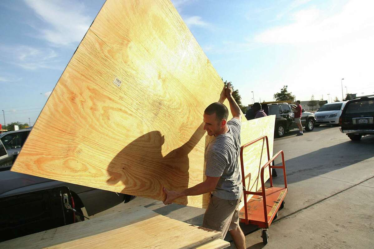 Eric Trevino, of Pearland, loads plywood into his truck at Home Depot in preparation for Hurricane Ike in 2008.