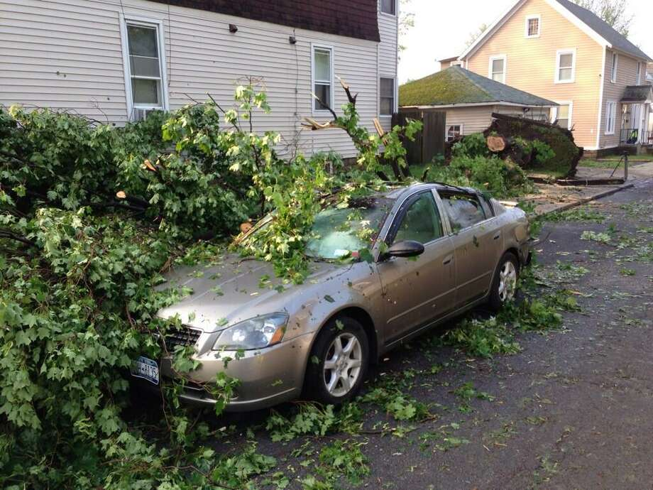 A car was severely damaged when a tree fell on it at the corner of 9th and Campbell in Schenectady. (Skip Dickstein / Times Union)