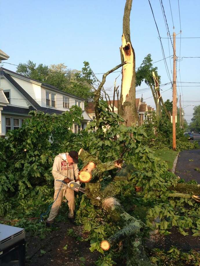 Campbell Avenue in Schenectady has numerous trees down. Hubert Steinly Jr removes trees from neighbor's driveway on Thursday, May 30, 2013. (Skip Dickstein / Times Union)
