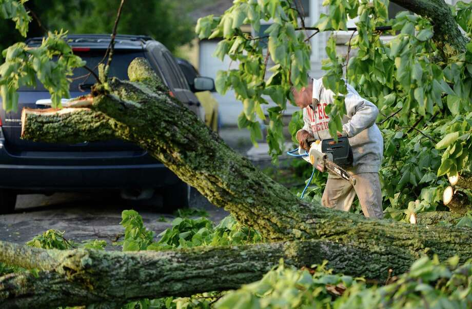 Hubert Steinly Jr. removes trees from his neighbors driveway on Campbell Avenue May 31, 2013 after a storm hit the area in Schenectady, N.Y. Photo: Skip Dickstein