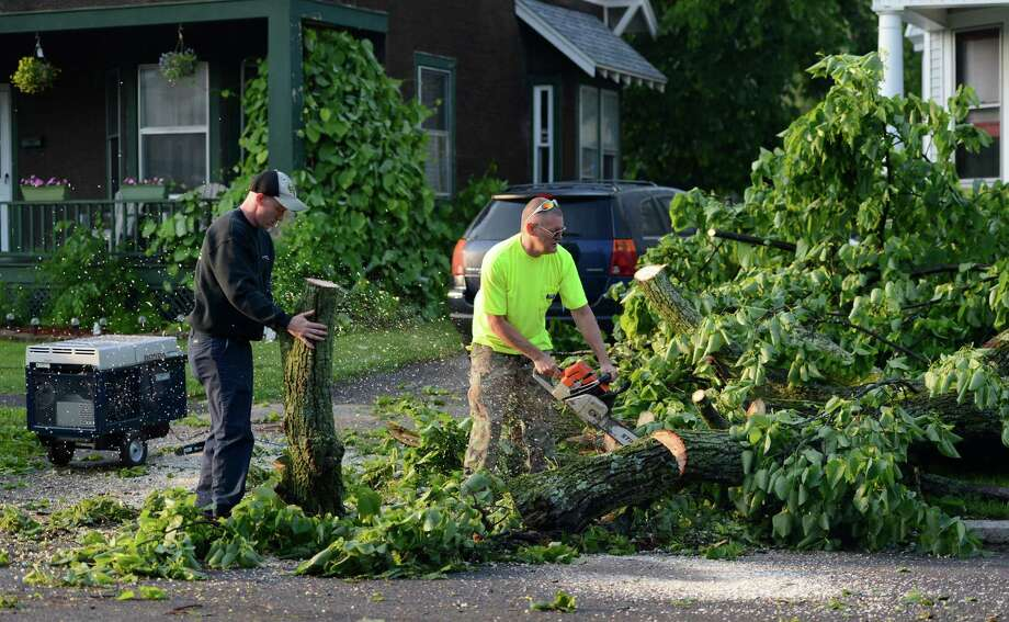 Good samaritans removes trees from a neighbors driveway on Campbell Avenue May 31, 2013 after a storm hit the area in Schenectady, N.Y. Photo: Skip Dickstein