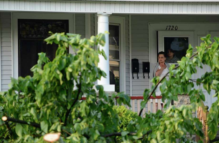 A homeowner looks out as people clear trees from a neighbors driveway on Campbell Avenue May 31, 2013 after a storm hit the area in Schenectady, N.Y. Photo: Skip Dickstein