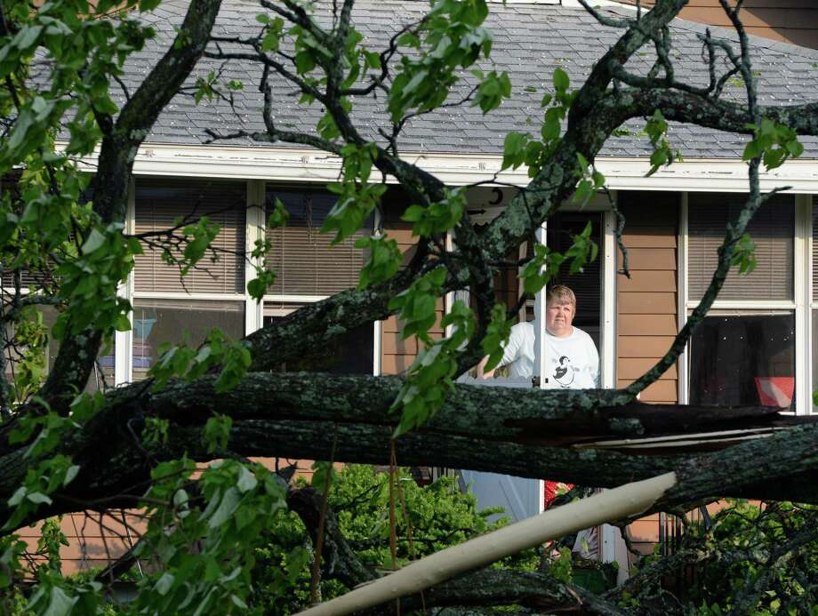 A woman  who identified herself as Kim looks out at the damage on Perry Street May 31, 2013 after a storm hit the area in Schenectady, N.Y. Photo: Skip Dickstein