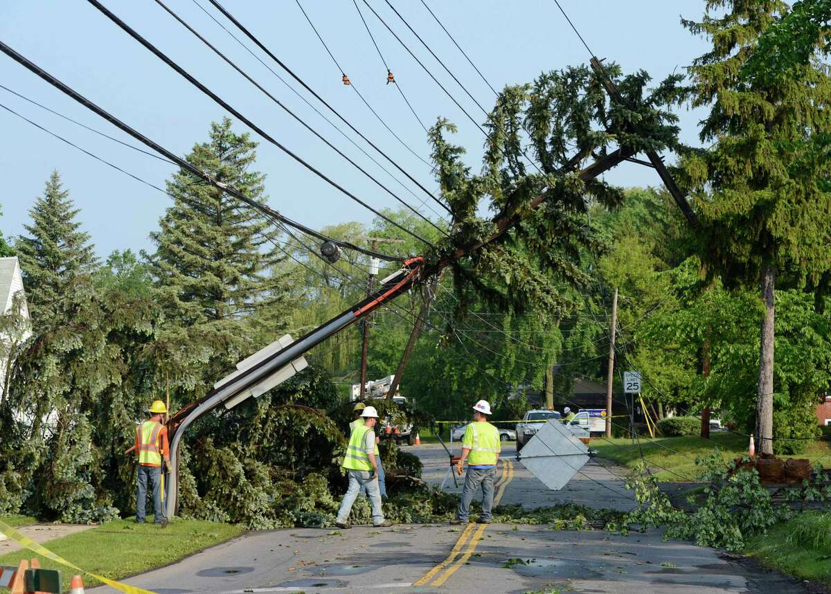 National Grid and City of Schenectady workers asses the damage to a power pole as it is held from the ground by lines May 30, 2013 after a storm hit the area in Schenectady, N.Y. (Skip Dickstein / Times Union)