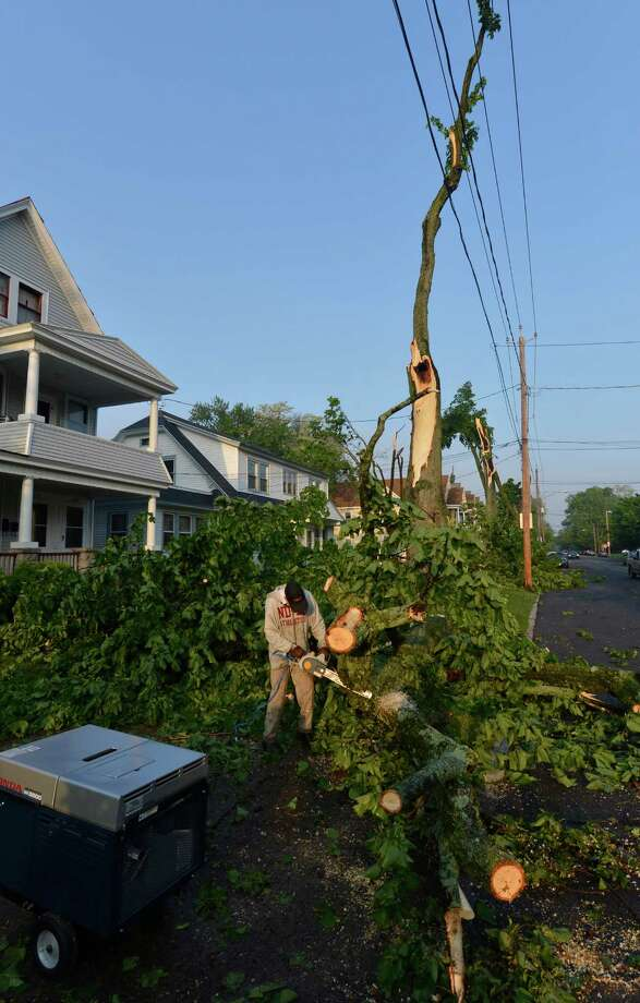 Hubert Steinly Jr. removes trees from a neighbors driveway on Campbell Avenue May 31, 2013 after a storm hit the area in Schenectady, N.Y. Photo: Skip Dickstein