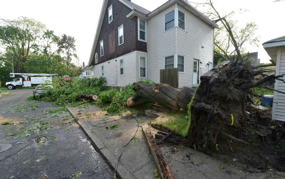 An uprooted tree caused damage to a car and sidewalk on Ninth Ave May 31, 2013 after a storm hit the area in Schenectady, N.Y. Photo: Skip Dickstein
