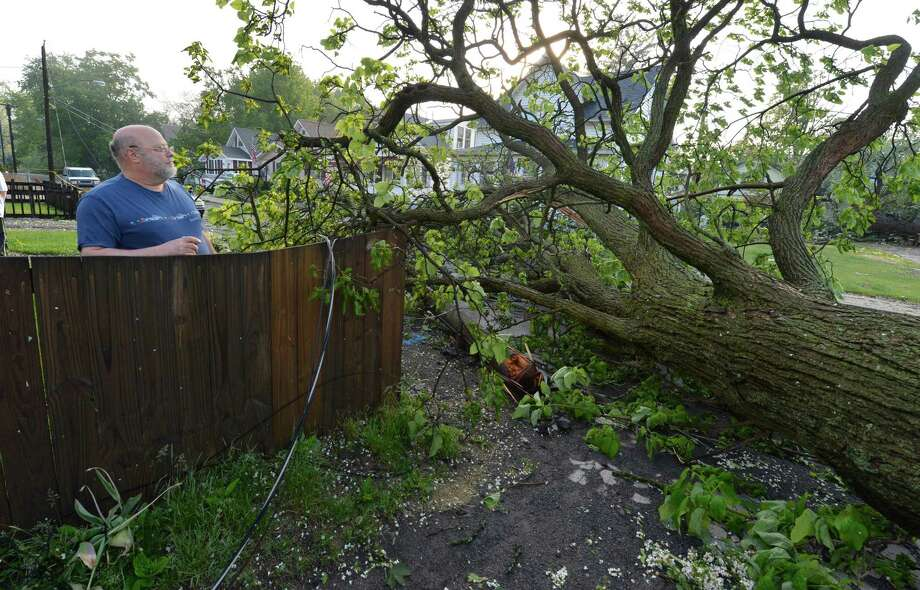 Homeowner Emmett Inserra looks over at a tree as it lies in the middle of Perry Street May 31, 2013 after a storm hit the area in Schenectady, N.Y. Photo: Skip Dickstein