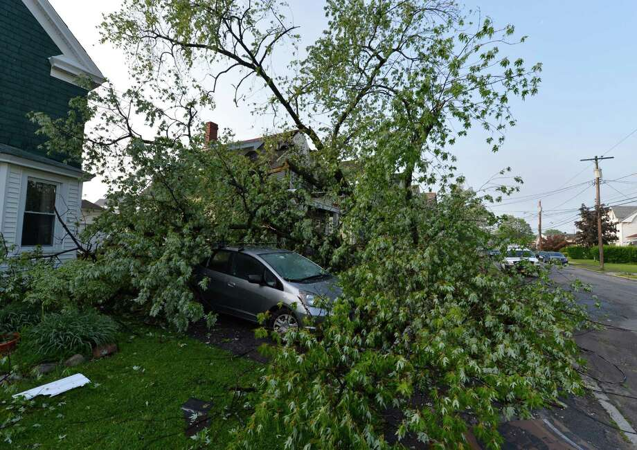A tree lies on a car and caused damage to home at 417 and 421 Perry Street May 31, 2013 after a storm hit the area in Schenectady, N.Y. Photo: Skip Dickstein