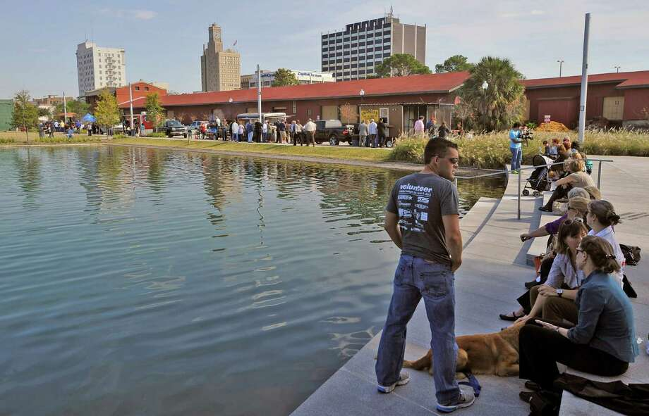 Quite a few of the lunch goers enjoyed their lunch amid the sunshine and water sitting on the steps close to the lake. The food vendors are in the background. Monday November 19, 2012 was the first of three scheduled Lunch at the Lake events at the new downtown Event Centre. The City of Beaumont provided the music, seating, and scenery, and visitors could get lunch from one of these food vendors that were on site like Big Bo's barbecue, Charles Brewer barbecue, Rao's pizza and gelato, Terrell's ice cream, Wise Guys Grill burgers and fries, and Zummo's sausage and boudain. Others even ordered in advance from Katharine & Co. for their lunches.  Dave Ryan/The Enterprise Photo: Dave Ryan