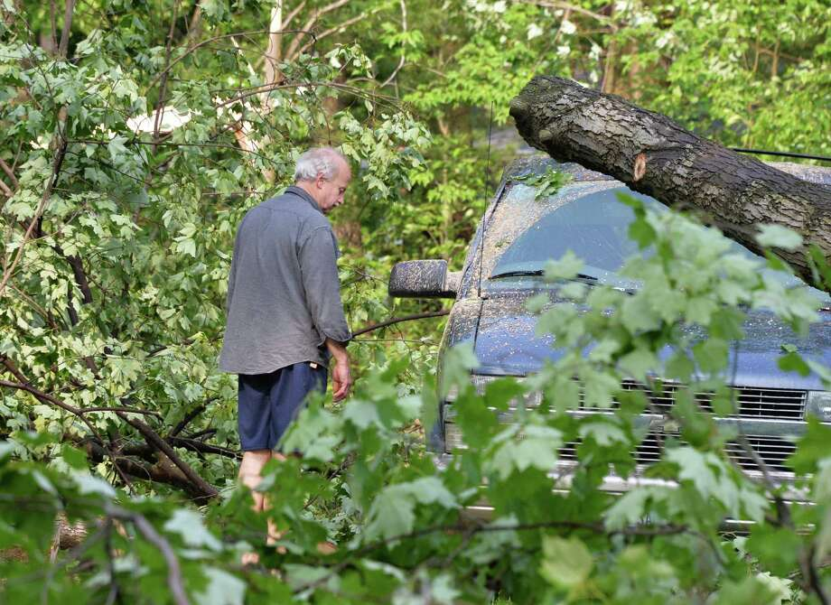 Peter Hagner looks over damage to his van from yesterday's storm at his home on Guadalupe Pass in Clifton Park Thursday May 30, 2013. Hard hit, the neighborhood remains without power.  (John Carl D'Annibale / Times Union) Photo: John Carl D'Annibale