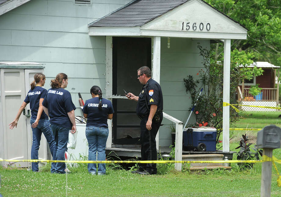 Crime scene investigators at the Hamshire home where a woman was shot Thursday morning. The Jefferson County Sheriff's Department is conducting an investigation to the incident.  Photo taken Thursday, May 23, 2013 Guiseppe Barranco/The Enterprise Photo: Guiseppe Barranco, STAFF PHOTOGRAPHER / The Beaumont Enterprise
