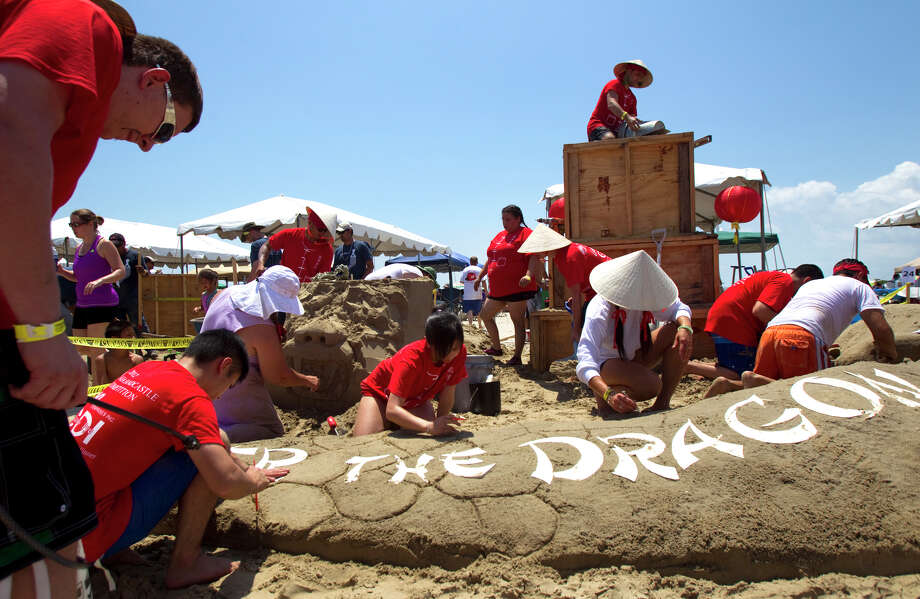 "A team works on their sand sculpture themed ""Enter the Dragon"" during the 26th annual AIA SandCastle Competition on Galveston's East Beach Saturday, June 2, 2012, in Galveston. Photo: Cody Duty, Houston Chronicle / © 2011 Houston Chronicle"