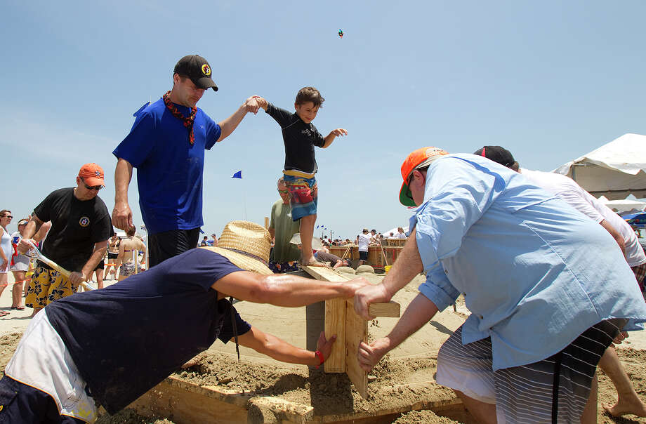 Hunter Uptmor, 6, holds his father, Craig's hand as they build their sand sculpture during the 26th annual AIA SandCastle Competition on Galveston's East Beach Saturday, June 2, 2012, in Galveston. Photo: Cody Duty, Houston Chronicle / © 2011 Houston Chronicle