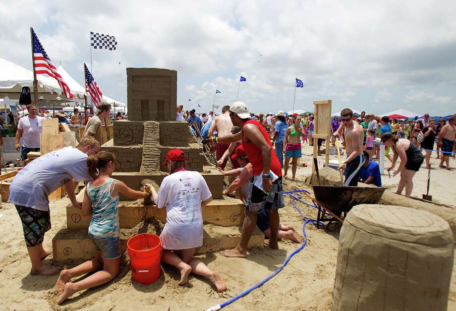 "A team works on their sand sculpture themed ""2012 Is This The End...?"" during the 26th annual AIA SandCastle Competition on Galveston's East Beach Saturday, June 2, 2012, in Galveston. The event brought out over 60 teams with the winner receiving the Gold Bucket Award. Each team used different tools ranging from shovels, just their hands and feet, and customized tools to shape their castles. The judging of all sculptures is rated on originality of concept, artistic execution of the concept, technical difficulty, carving technique, and utilization of the site. (Cody Duty / Houston Chronicle) Photo: Cody Duty / © 2011 Houston Chronicle"