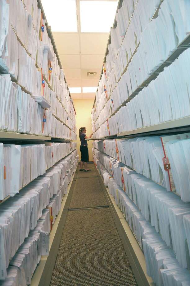 Over at Baptist Hospital's Medical Records department, Toni Kennedy, an indexing technician, works among an aisle full of records that are being kept for a 90 day waiting period, before being shredded. Local hospitals and health care organizations announced Wednesday that they have joined together to launch a regional health information network that will improve care, increase safety, reduce costs and eliminate long term storage of redundant paper records. This network will link patients' information, with various health care providers in the system. Dave Ryan/The Enterprise Photo: Dave Ryan