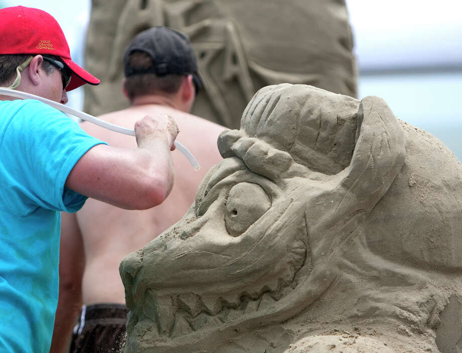 Stephen Jones puts the finishing touches on a wolf sculpture made from sand during the 26th annual AIA SandCastle Competition on Galveston's East Beach Saturday, June 2, 2012, in Galveston. Photo: Cody Duty, Houston Chronicle / © 2011 Houston Chronicle